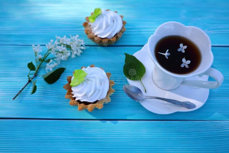 Una tazza bianca di tè e di pasticceria immagine stock