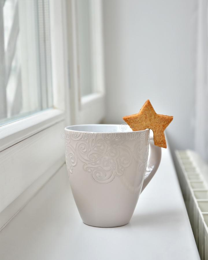 Una tazza bianca di tè o una tazza di caffè con un biscotto sotto forma di una stella dalla finestra immagine stock