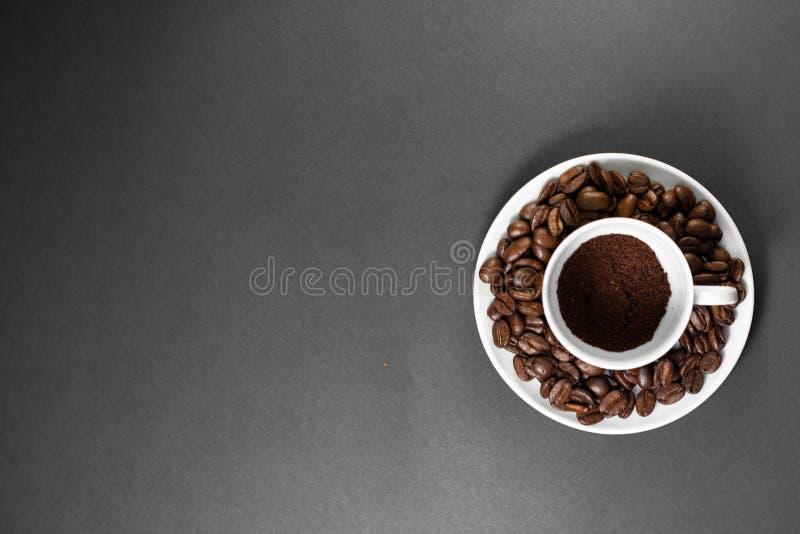 una tazza con i chicchi di caffè arrostiti di recente a terra con frutta dalla pianta del caffè con un piatto fotografia stock