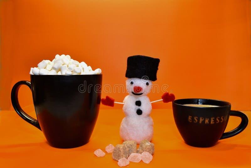 Una tazza dei supporti del caffè del caffè espresso accanto ad un pupazzo di neve divertente fotografia stock libera da diritti