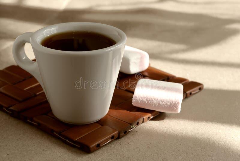 Una tazza del caffè d'invigorimento aromatico di mattina su un supporto di legno di vimini immagini stock