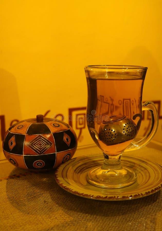 Una tazza del tè caldo della camomilla con il filtro sveglio dalla foglia di tè in tazza trasparente e vaso di legno peruviano de fotografia stock