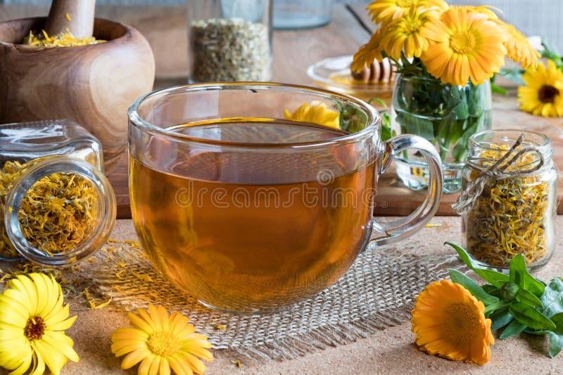 Una tazza del tè della calendula con la calendula fiorisce nei precedenti fotografia stock libera da diritti