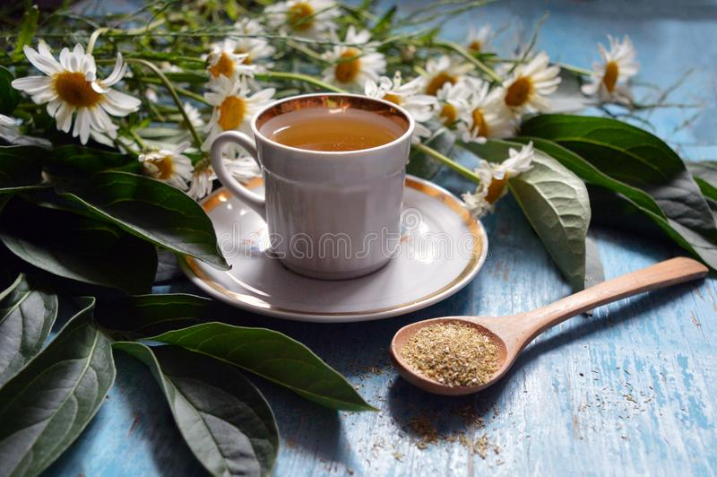 Una tazza del tè di camomilla su un fondo di legno fotografia stock