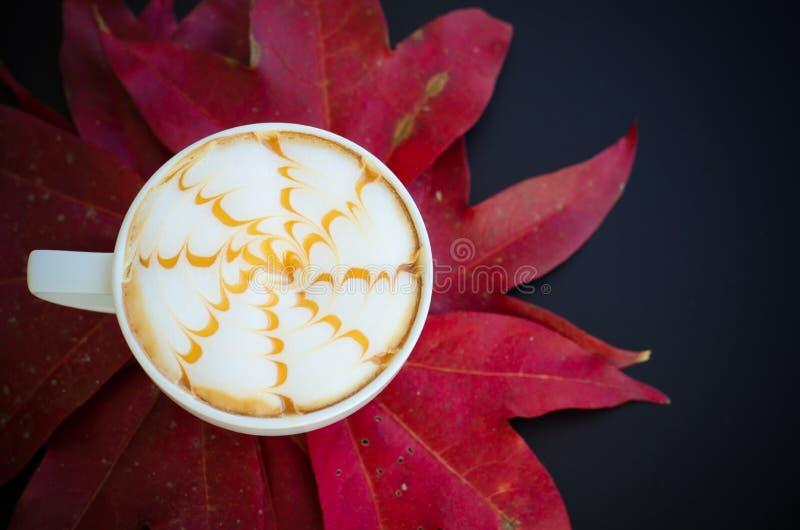 Una tazza di arte del latte e delle foglie di acero fotografie stock libere da diritti