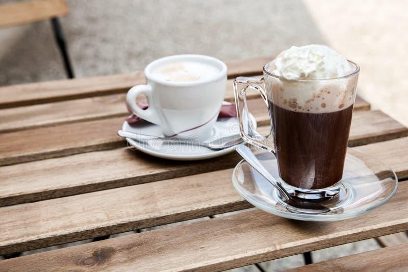Una tazza di cacao caldo con panna montata sulla tavola fotografia stock