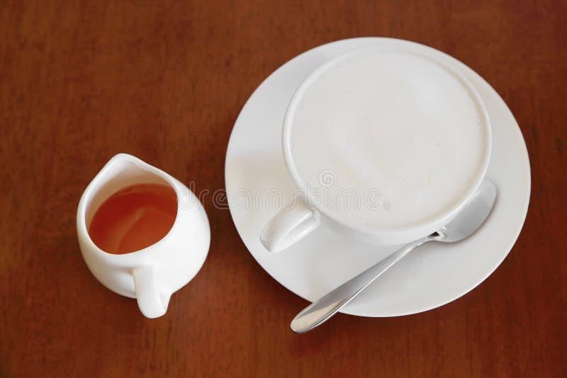 Una tazza di caffè caldo con la schiuma del latte e di miele su fondo di legno fotografie stock