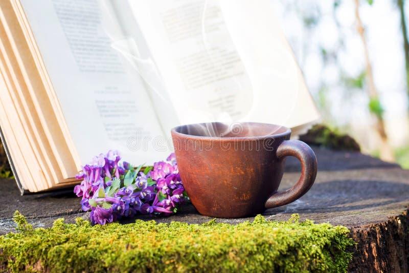 Una tazza di caffè caldo nel legno su un ceppo accanto ad un libro aperto Resto nei libri di lettura della foresta nel legno nel  fotografia stock