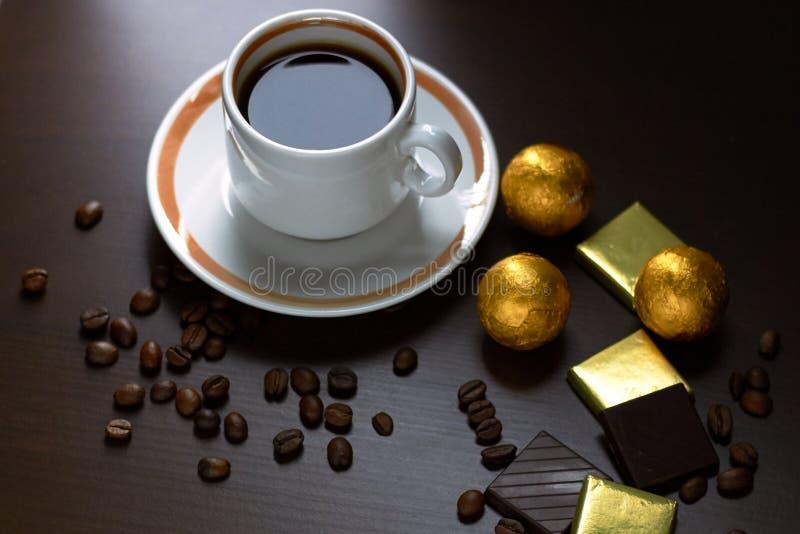 Una tazza di caffè con fagioli sparpagliati e barrette di cioccolato, dolci e caramelle in involucri d'oro su banco di legno marr immagine stock