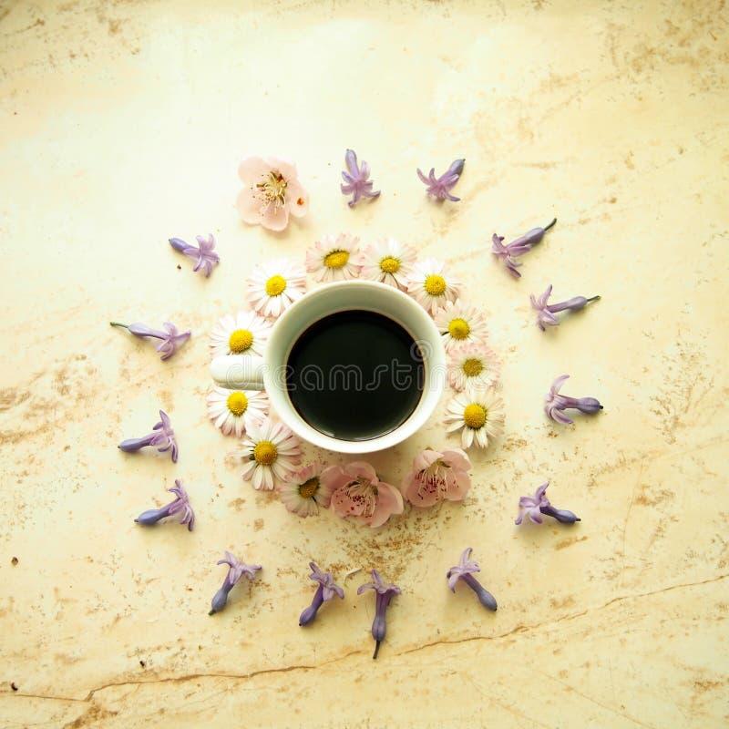 Una tazza di caffè con i fiori della molla fotografia stock libera da diritti