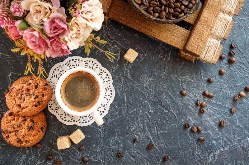 Una tazza di caffè con i pezzi di zucchero di canna, di biscotti con cioccolato e di vaso con i chicchi di caffè top fotografie stock