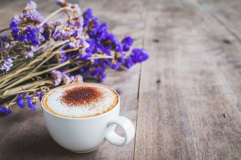Una tazza di caffè con il mazzo della viola ha asciugato i fiori sulla f di legno fotografia stock libera da diritti