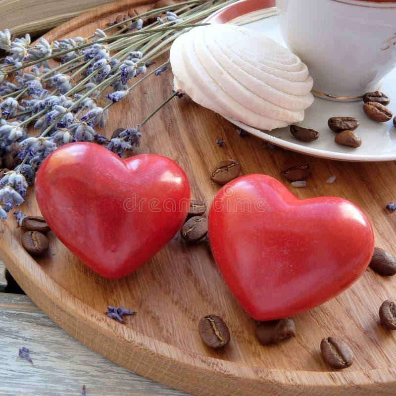 Una tazza di caffè con le caramelle gommosa e molle su un vassoio di legno immagine stock