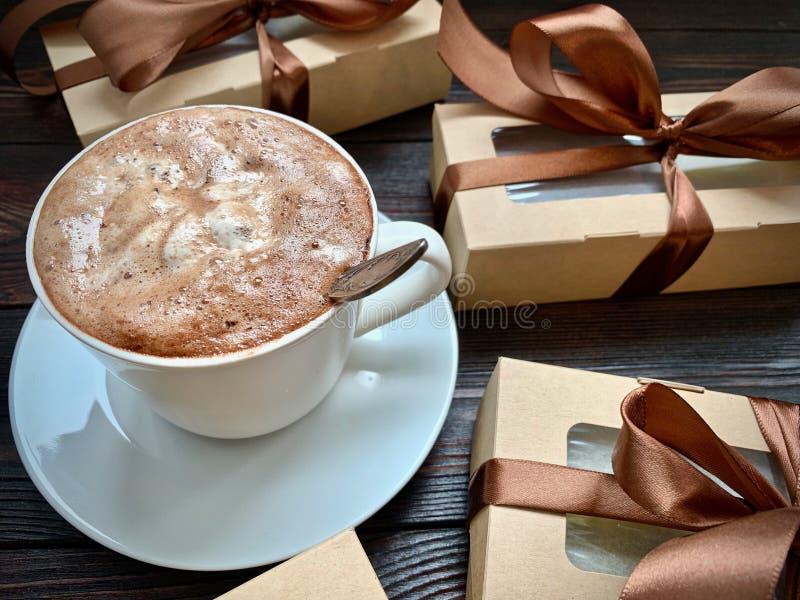 Una tazza di caffè con schiuma sulla tavola, contenitori di regalo con un arco immagine stock
