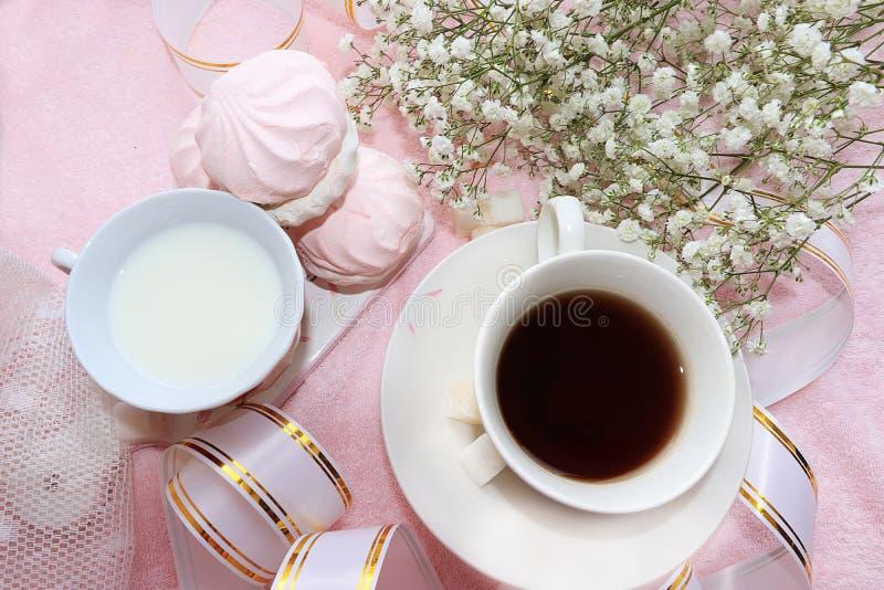 Una tazza di caffè e una tazza di latte sulla tavola di mattina, sul dessert e sui fiori della molla fotografie stock libere da diritti