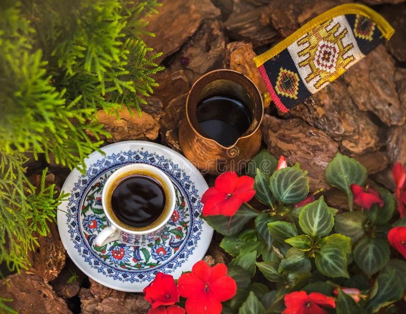 Una tazza di caffè e un jezva stanno fra i fiori nel giardino fotografia stock