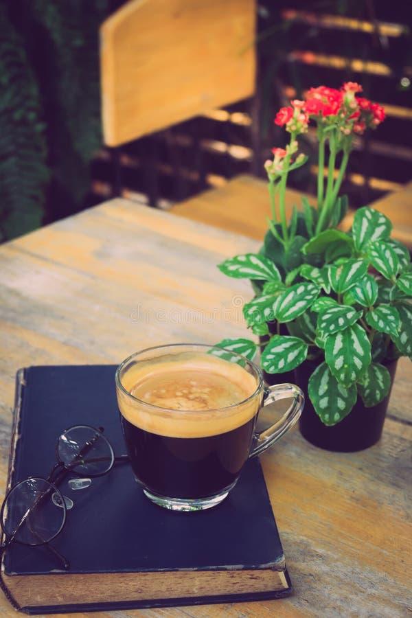 Una tazza di caffè nero con i vetri al libro sulla tavola in giardino fotografie stock libere da diritti