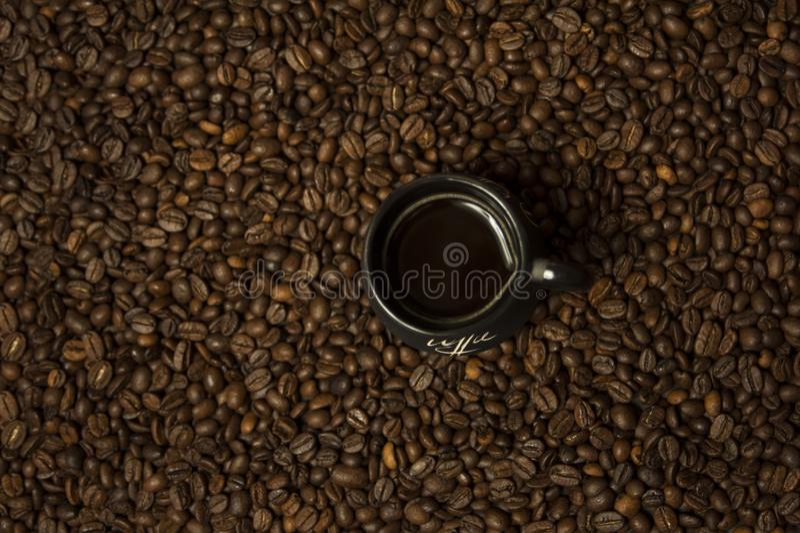 Una tazza di caffè nero con latte che sta sui chicchi di caffè Un concetto sano della prima colazione immagini stock
