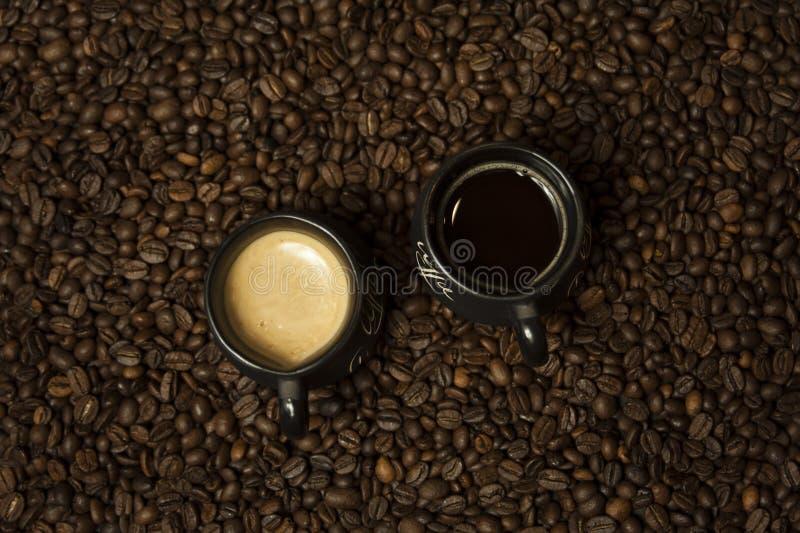 Una tazza di caffè nero con latte che sta sui chicchi di caffè Un concetto sano della prima colazione fotografia stock libera da diritti