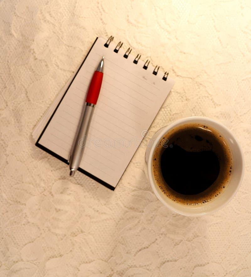 Una tazza di caffè nero, del taccuino e di una penna a sfera immagine stock