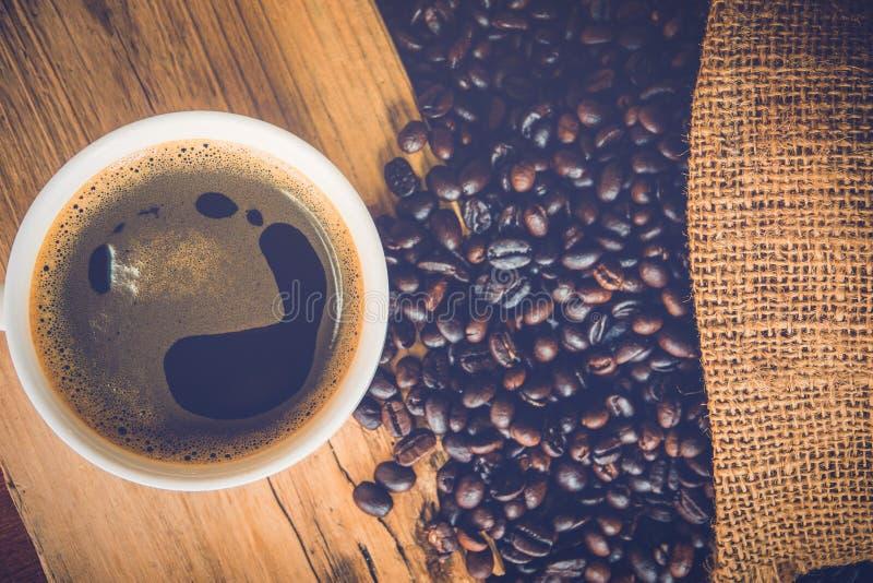 Una tazza di caffè nero in tazza bianca con il chicco di caffè nella borsa del sacco fotografia stock libera da diritti