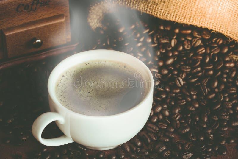 Una tazza di caffè nero in tazza bianca con il chicco di caffè in parte posteriore del sacco immagini stock libere da diritti