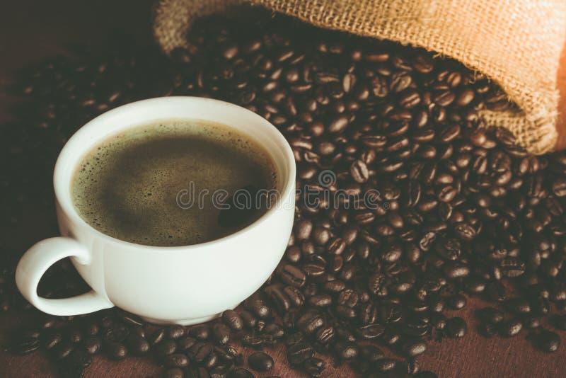 Una tazza di caffè nero in tazza bianca con il chicco di caffè in parte posteriore del sacco fotografie stock libere da diritti