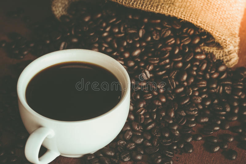 Una tazza di caffè nero in tazza bianca con il chicco di caffè in parte posteriore del sacco fotografia stock libera da diritti