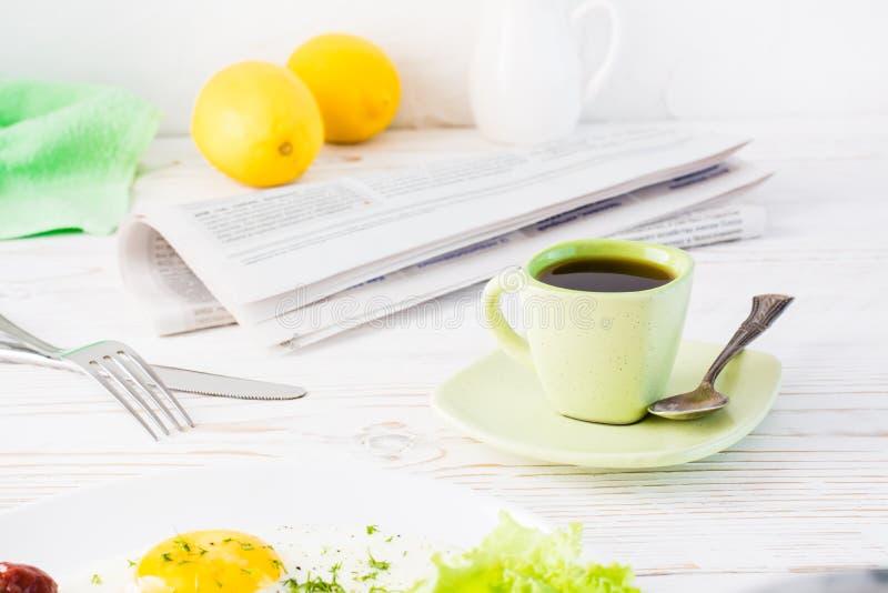 Una tazza di caffè nero, di un giornale e della coltelleria su una tavola bianca fotografia stock