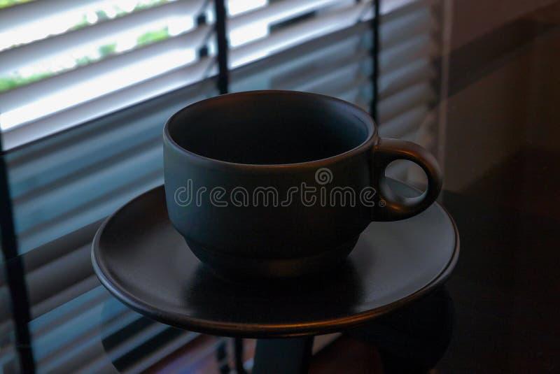 Una tazza di caffè nero vuota è sulla tavola di vetro accanto alla finestra fotografie stock