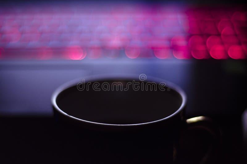 Una tazza di caffè o un tè davanti ad una tastiera luminosa del computer portatile fotografia stock