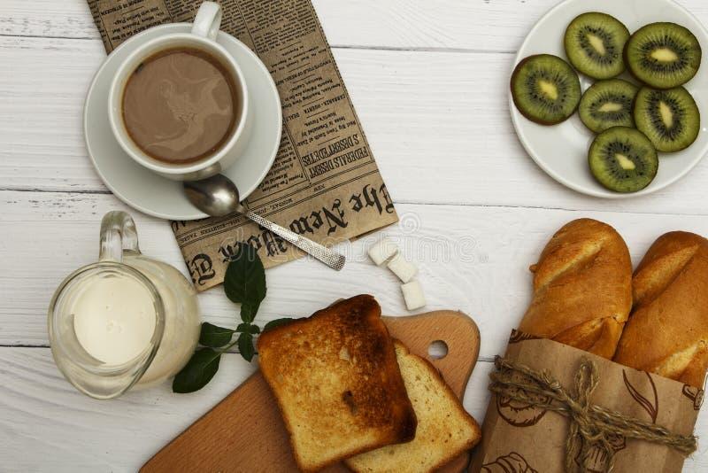 Una tazza di caffè, pane fresco, pane tostato su un fondo legnoso bianco Pane fresco della prima colazione di mattina con una taz immagini stock libere da diritti