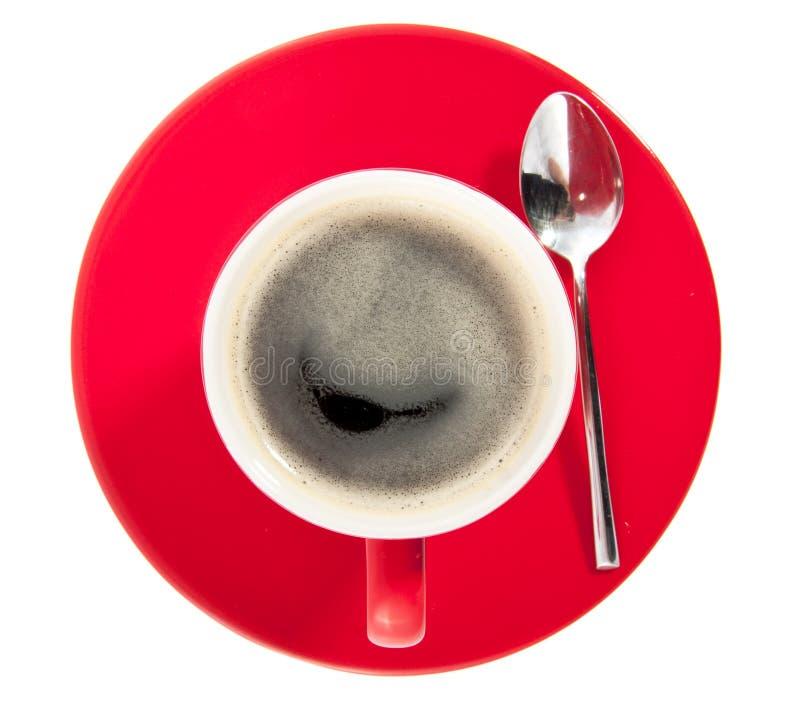 Una tazza di caffè rossa su un piattino immagine stock