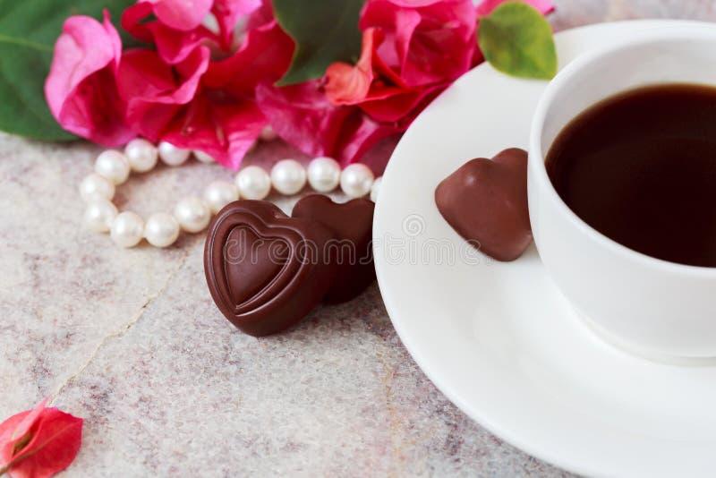 Una tazza di caffè su un fondo di marmo accanto ai fiori rosa, perle bianche, caramella sotto forma di cuore St Giorno del ` s de fotografia stock