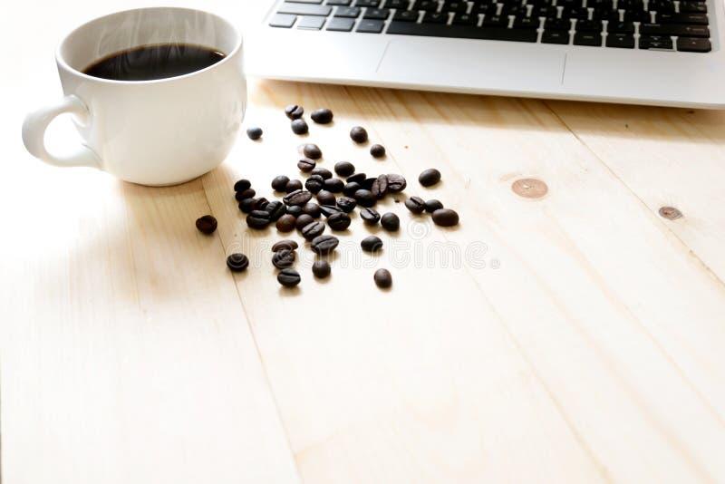 Una tazza di caffè, un computer portatile e un caffè spanto fotografie stock libere da diritti