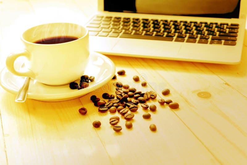 Una tazza di caffè, un computer portatile e un caffè spanto fotografie stock