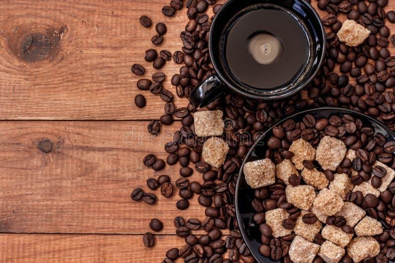 Una tazza di caffè, uno zucchero di canna ed i chicchi di caffè sulla tavola di legno immagine stock