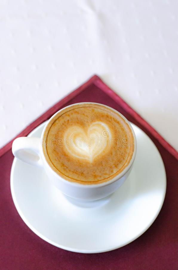 Una tazza di cappuccino con una schiuma e un modello in forma di cuore fotografia stock