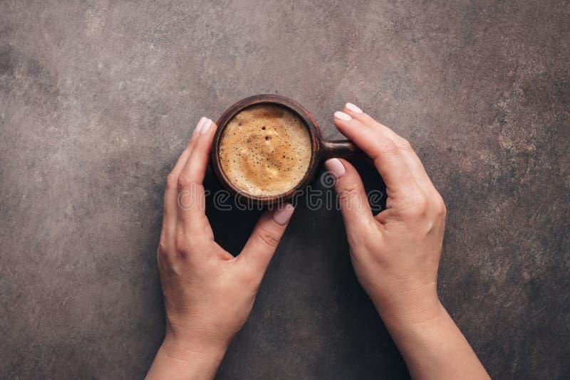 Una tazza di delizioso caffè cappuccino in mani femminili, fondo rustico scuro, vista dall'alto immagine stock