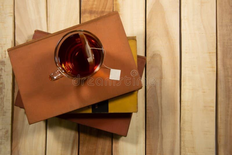 Una tazza di tè è situata sul libro Ed insieme su una composizione in tavola di legno con lo spazio della copia su fondo di legno immagine stock libera da diritti