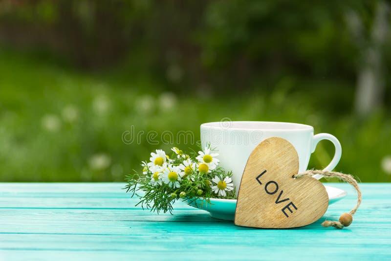 Una tazza di tè caldo fragrante con le erbe e un cuore di legno Una bevanda calda utile con i fiori della camomilla Medicina natu immagine stock libera da diritti