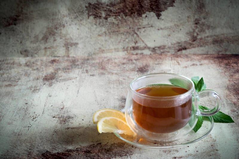 Una tazza di tè con il limone e un ramoscello della menta su un bello fondo immagini stock libere da diritti
