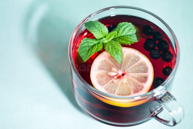 Una tazza di tè con la menta e un limone fotografie stock libere da diritti