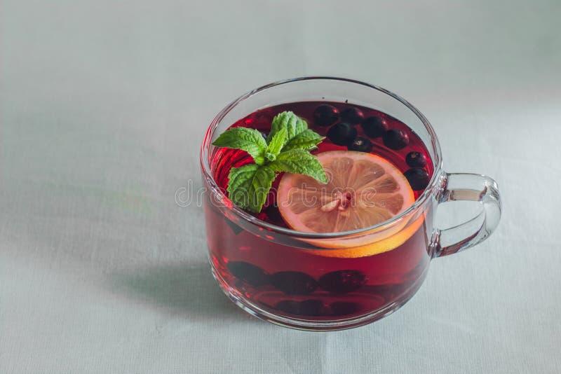 Una tazza di tè con la menta e un limone fotografie stock