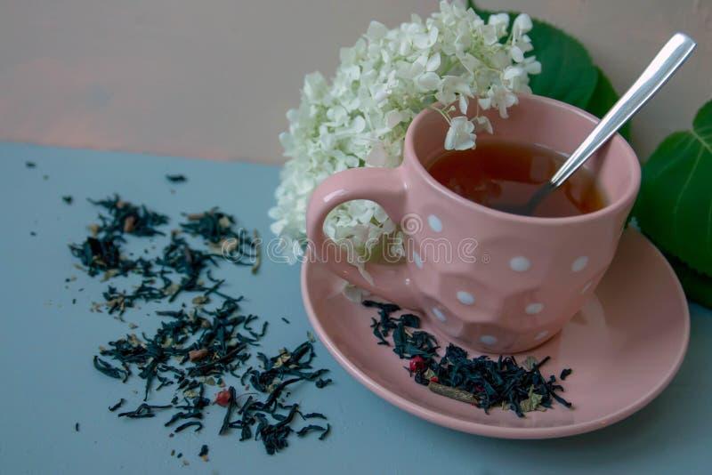 Una tazza di tè contro i precedenti, dei fiori e del tè sbriciolato immagini stock libere da diritti