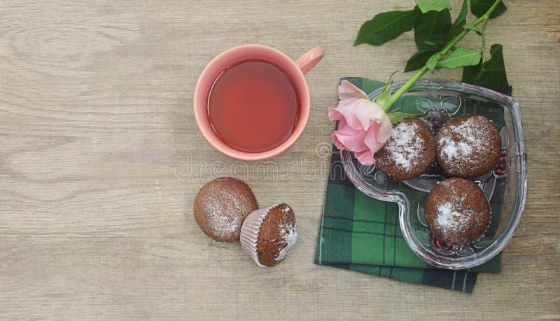 Una tazza di tè, dei muffin del cioccolato in un vaso di vetro una forma del cuore e di un rosa è aumentato su un fondo di legno immagini stock libere da diritti