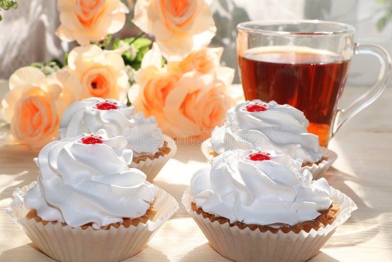 Una tazza di tè e un dolce su una tavola soleggiata, un mazzo dei fiori della molla per l'umore, fotografia stock libera da diritti