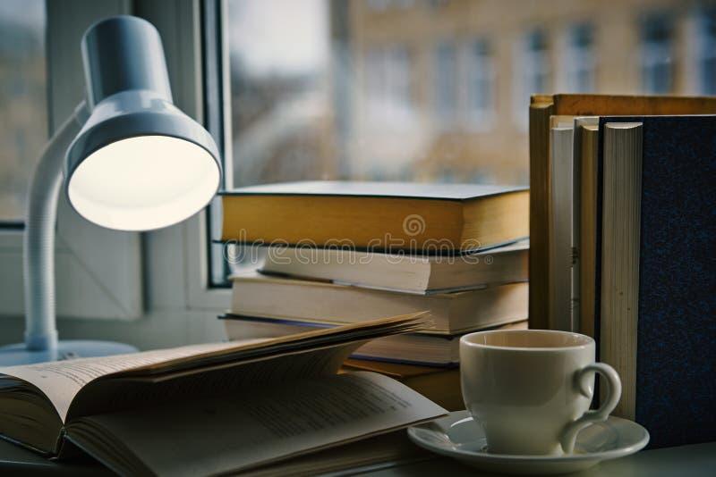 Una tazza di tè, libro aperto sotto la lampada fotografia stock