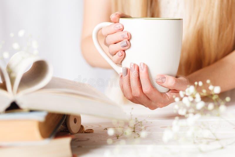 Una tazza di tè in mani delle donne Concetto per la mattina della molla Tè del fiore in una tazza bianca sulla tavola con i libri fotografie stock libere da diritti