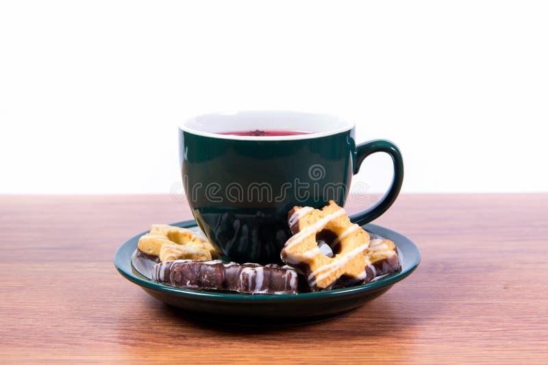 Una tazza di tè nero fragrante in una tazza ed in un biscotto al burro della porcellana coperti di cioccolato su un piatto - prim fotografia stock